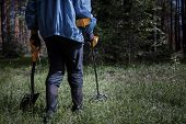 A man with a metal detector in the woods looking for vintage items and valuable coins poster