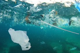 Plastic pollution in ocean. Plastic bags, straws and bottles pollute sea. Underwater trash photo