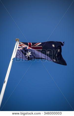 Australian Flag Flying In The Breeze Against Clear Blue Sky