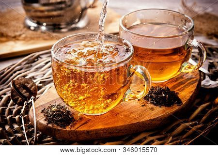 Two Cups Of Black Tea On A Wicker Table Early In The Morning. Tea Morning At Dawn. The Process Of Po