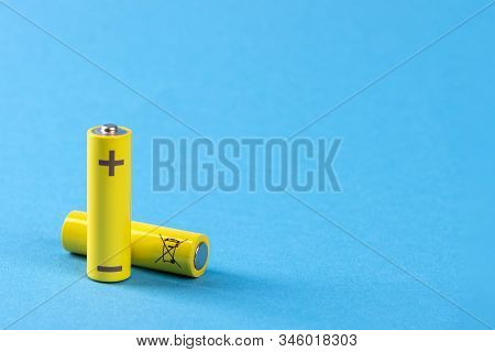 Two Yellow Batteries On A Blue Background With Place For Text