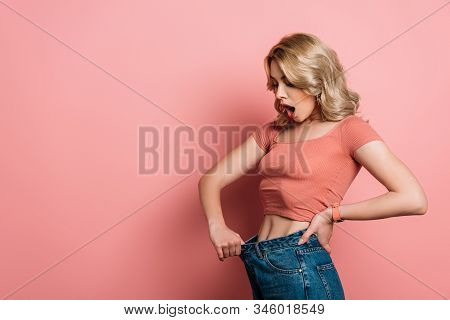 Discouraged Girl Wearing Oversize Jeans On Pink Background