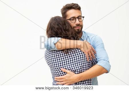 Happy Young Couple In Love Hugging. Cheerful Young Man And Woman Hugging While Standing On White Bac