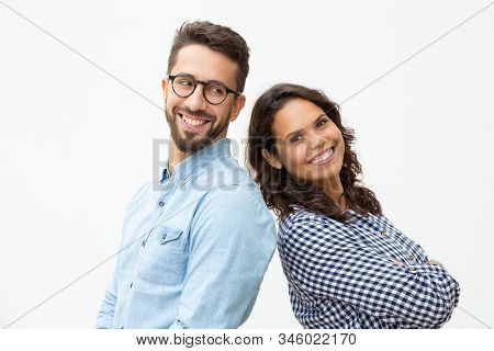 Content Man And Woman Standing Back To Back. Side View Of Cheerful Young Couple Standing Together An