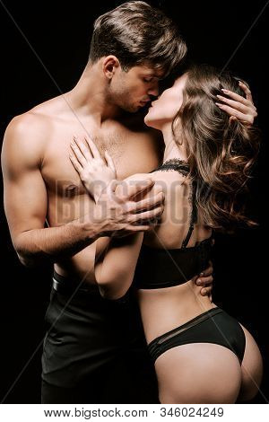 Seductive Man And Passionate Woman In Underwear Kissing Isolated On Black