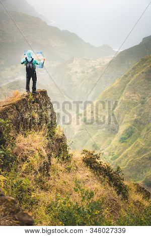 Alone Hiker With Map Of The Island Staying On A Rocky Ledge In Front Of A Gorgeous Panorama View Of