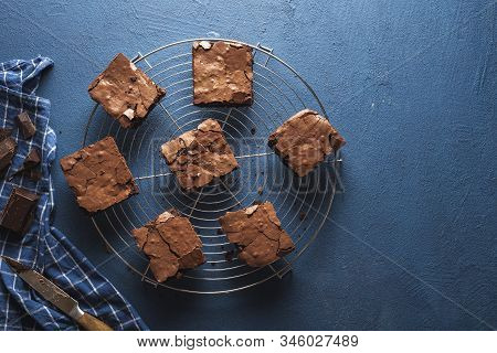 Chocolate Brownies Squares On A Cooling Tray, A Blue Kitchen Towel, On A Classic Blue Table. Freshly