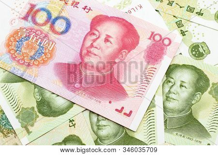 A Close Up Image Of A Red, One Hundred Chinese Yuan Bank Note, Close Up On A Background Of Green One