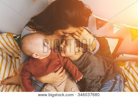 Young Beautiful Mother With Her Children On The Bed, Tightly Hugs Her Son And Little Daughter, Kisse