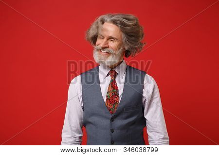 Smiling Elderly Gray-haired Mustache Bearded Man In Classic Shirt Vest Tie Posing Isolated On Red Ba