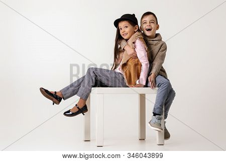 Cute Happy Stylish Little Couple Child Girl And Boy In Fashionable Clothes Sittting Together At Stud