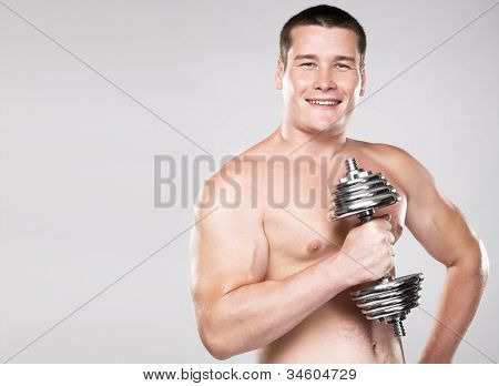 Athletic man lifting a dumbbell, studio photo