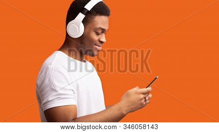 Enjoy Music. Smiling Afro Guy Listening To Podcast On Cellphone Using Headphone Set, Orange Studio B