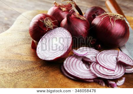 Red Onions Circles And Homegrown Red Onions On Board Against Wooden Background