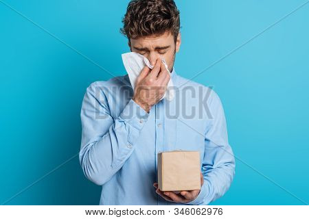 Diseased Young Man Sneezing In Paper Napkin On Blue Background