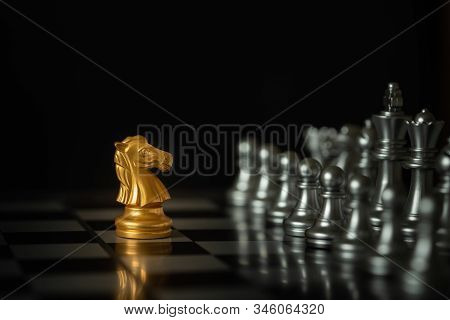 Gold Knight Chess Stands On Chessboard In Front Of Opponents On Dark Background With Copy Space. Bus