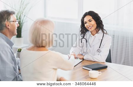 General Practitioner. Mexican Female Physician And Senior Couple Patients Handshaking At Doctors Off