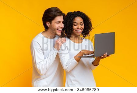Online Sales Concept. Happy Interracial Spouses Holding Laptop And Looking At Computer Screen With E