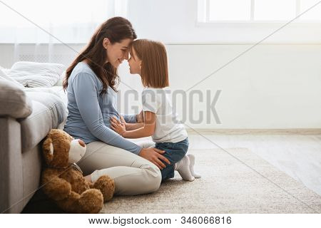 Family Concept. Adorable Little Girl Cuddling With Her Pregnant Mother At Home, Copy Space