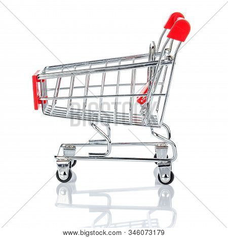 Side View Of Empty Chromed Toy Market Shopping Cart With Red Handle And Plastic Board On The Front.