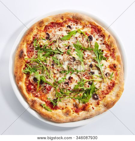 Pizza with tuna, black olives and fresh arugula on white restaurant plate isolated. Traditional italian seafood pizza with yellowfin meat, delicious fast food with fish top view