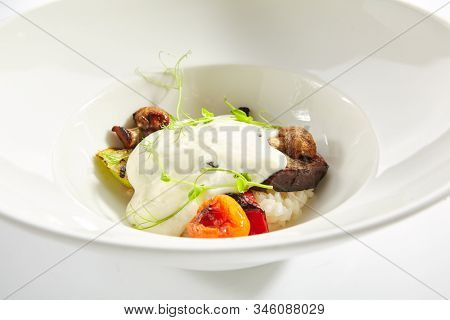 Risotto with grilled vegetables, carnaroli rice and cheese foam on white restaurant plate isolated. Traditional Italy rissoto or vegetable paella with cooked eggplants, mushrooms and greens closeup