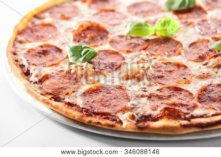 Traditional italian pepperoni pizza with salami, chili pepper, mozzarella cheese, fresh basil, tomatoes and tomato sauce isolated. Delicious italy salami flatbread cutout, tasty fast food closeup