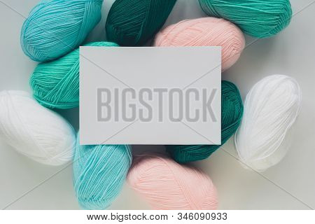 White Paper Sheet On Acrylic Soft Pastel Colored Wool Yarn Thread Skeins Heap On White Background, T