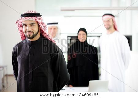 Confident muslim  young business executive with his team in the background
