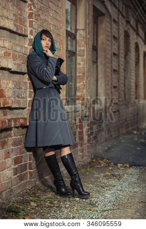 Young fashion woman with handbag leaning on brick wall Stylish female model in gray classic coat and head scarf