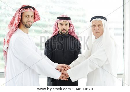 Arabic business team showing unity with their hands together