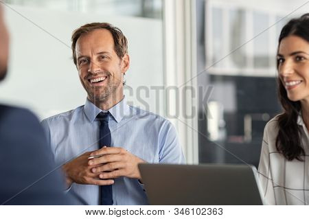 Business partners discussing ideas at meeting. Successful businessman listening to colleague during meeting in modern office. Happy mature business man and businesswoman smiling during brainstorming.