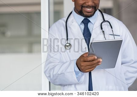 Mature black doctor using digital tablet at hospital. Close up of smiling doctor at private clinic reading medical exam on tablet. Practitioner holding digital report for patient's health record.