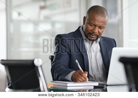 African serious businessman writing notes and using laptop. Mature business man writing his strategy in modern office. Focused black entrepreneur sitting at desk in modern office while working.