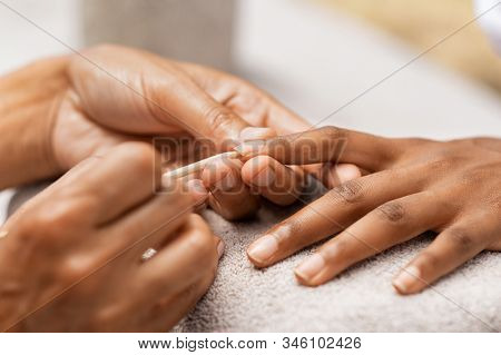 Close up of beautician hands cleaning nails with equipment. Hands of woman getting manicure treatment. Close up of manicurist pushing cuticles on nails with wooden stick for cuticle in beauty salon.
