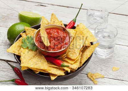 Mexican nachos chips with salsa sauce and tequila shots on wooden table
