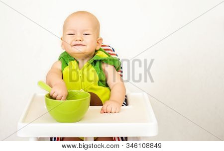 Little Happy Baby With Spoon Sits At Highchair And Eats Porridge On Plate