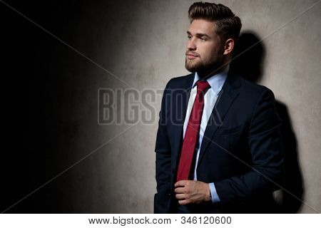 side view of an elegant formal guy wearing navy suit standing with hand in pocket and grabbing his tie serious on gray studio background