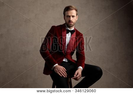 Bothered model looking forward while wearing tuxedo and sitting on a stool on brown studio background