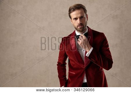 Bothered elegant man fixing his bowtie while wearing tuxedo and standing on brown studio background