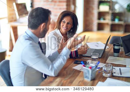 Two middle age business workers smiling happy and confident. Working together with smile on face using laptop at the office