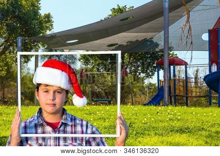 Boy in Santa Claus hat smiling holding a frame in his hands. Children 's playground with a multicolored attractions. The concept of physical and mental development of children