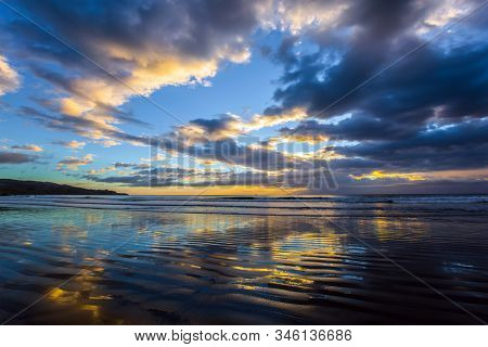 Morning Calm. Gentle cloud colors are reflected in the ocean water. Light wind causes small ripples in the water. New Zealand, Pacific Coast. The concept of artistic photography