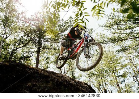 Downhill Mountain Biking Rider Jump Hill In Sunlight