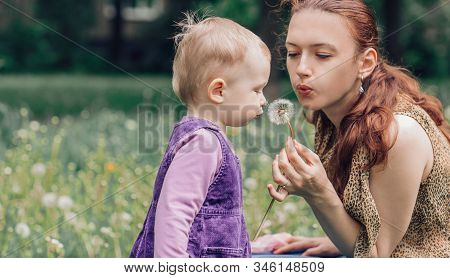 Young Mom With Her Little Daughter Blowing On A Dandelion