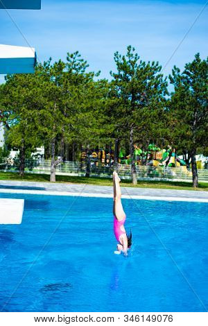 Swan Dive. Little Caucasian Female 8 Years Old Girl Diving From 5 Mether Diving Platform.
