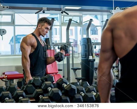 Man Looks In Mirror While Exercises With Dumbbells