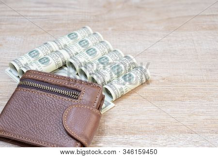 Us Dollar Banknotes With Brown Leather Wallet On The Wooden Floor Background