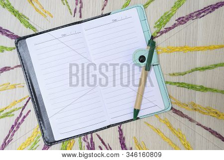 Top View With Notebook, Pen And Dried Rice Grains On Wooden Floor