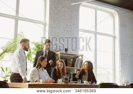 Positive. Group Of Young Business Professionals Having A Meeting. Diverse Group Of Coworkers Discuss
